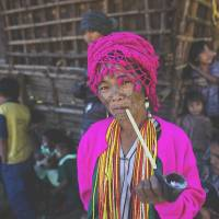 Half-time break: An ethnic Chin woman with a traditional tattooed face, who is a member of Myanmar's Maun subtribe, smokes a pipe during a local soccer tournament in the Chin state village of Kyar Do on Dec. 18. | AP