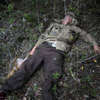 Overcome: Forensic archaeologist Dannal Aramburu lies on the forest ground exhausted but relieved after having been separated for about three hours from colleagues walking to a site of mass graves in remote Chungui, Peru, on Nov. 9. | AP