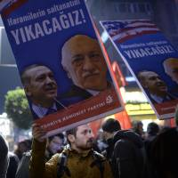 Growing discontent: A Turkish protester holds up a placard with pictures of Prime Minister Recep Tayyip Erdogan (left) and cleric Fethullah Gulen with the slogan 'We will cast them down' during a demonstration against corruption in Istanbul on Wednesday. | AFP-JIJI
