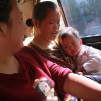 Womb for doubt: Wang Yuan watches as her mother-in-law, Yang Peiyun, comforts her daughter, Beibei, in a taxi in Zhuzhou, China. Beibei is more comfortable with her grandmother, who has raised her since she was 9 months old. | THE WASHINGTON POST