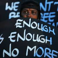 Out in force: An activist holds up a placard decrying violence against women during a demonstration in Bangalore, India, last December. | AFP-JIJI