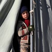 In need: A Syrian child looks out from his tent at a refugee camp in the Lebanese border town of Arsal on Friday. | AP