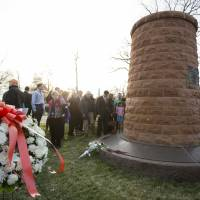 In memory of: Relatives and friends of the victims of the bombing of Pan Am Flight 103 gather around the memorial cairn at Arlington National Cemetery in Virginia on Saturday. | AP