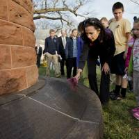 Not forgotten: Kit McGinnis offers flowers for her late sister-in-law, Louise Ann Rogers, at the Pan Am Flight 103 memorial cairn at Arlington National Cemetery on Saturday. | AP