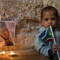 Shalom: Candles are placed in front of a picture of Nelson Mandela during a vigil by Palestinians and members of the African community in Jerusalem's Old City on Dec. 7. | AFP-JIJI