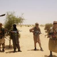 Allies: Fighters from Islamist group Ansar Dine, allied to al-Qaida in the Islamic Maghreb, stand guard during a hostage hand-over outside Timbuktu, Mali, on April 24, 2012. | AP