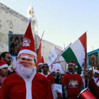 Stars of Bethlehem: Asian Christians in Santa Claus costumes march to the Church of the Nativity in Bethlehem, revered as the site of Jesus Christ's birth, on Wednesday. | AFP-JIJI