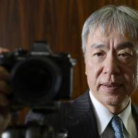 Still clicking: Hiroyuki Sasa, president and chief executive officer of scandal-tainted Olympus Corp., poses for a photograph with the OM-D E-M1 camera in Tokyo on Dec. 18. Sales of mirrorless models are growing at Olympus. | BLOOMBERG