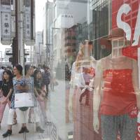 Doing what consumers do: Shoppers exit a clothing store in Tokyo's Ginza district Friday. | BLOOMBERG