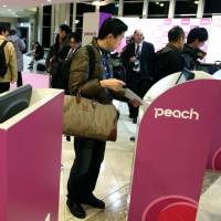 Just peachy: Passengers check-in for their flights at Peach Aviation Ltd.'s ticketing booth at Kansai International Airport on March 1, 2012.   BLOOMBERG