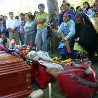 Simple dignity: Berta Quintreman, holding a plant in her hand, kneels next to the casket of her sister, Nicolasa, a Mapuche Indian leader, at her funeral Friday in Ralco, Chile. | AP