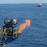 Eager for energy: A flare burns as methane hydrate gas is produced from drilling in the Nankai Trough about 50 km off the coast of Honshu in this handout photograph released March 12. | JAPAN OIL, GAS AND METALS NATIONAL CORP/BLOOMBERG