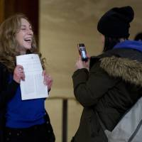 Standing up for rights: Valerie Scott, one of the three principles in the case, holds up the Canadian Supreme Court's ruling against all three of the nation's prostitution laws Friday in Ottawa. | AP