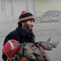 Combatants?: A man cries while holding the body of a child killed following some of the most sustained airstrikes by regime forces in Aleppo, Syria, on Sunday. | AP