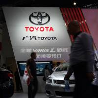 Venture offering: Visitors walk past the GAC Toyota Motor Co. booth at the Wuhan Motor Show 2013 in China in October. | BLOOMBERG