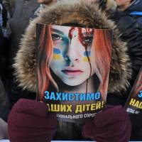 Protecting their interests: A protester holds up a poster criticizing police violence, reading 'Protect our Children,' during a rally in front of the Ukrainian parliament in Kiev on Tuesday. | AFP-JIJI