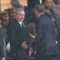 Chance clasped: U.S. President Barack Obama and Cuban President Raul Castro shake hands before a memorial service for Nelson Mandela on Tuesday in Johannesburg. | AP
