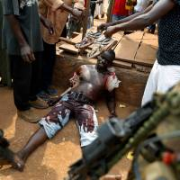 Bloody conflict: A suspected member of a Christian militia lies wounded from machete blows in the Kokoro neighborhood of Bangui, the capital of the Central African Republic, Monday. | AP