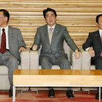 Same page: Prime Minister Shinzo Abe is flanked by Finance Minister Taro Aso (right) and Justice Minister Sadakazu Tanigaki in a Cabinet meeting Tuesday to adopt the 2014 budget. | KYODO