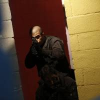Game plan: A Brazilian police officer takes part in a drill during a media presentation Tuesday in Rio de Janeiro to show off security training for the 2014 World Cup and 2016 Olympics. | AP