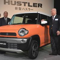 Bumper crop: Suzuki Motor Corp. President Osamu Suzuki (right) shows off the company's new Hustler mini sport utility vehicle at a news conference Tuesday in Tokyo. | AFP-JIJI