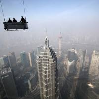 Thriving metropolis: Workers on a suspended platform prepare to clean the Shanghai World Financial Center on Jan. 30. The number of urban dwellers will nearly double over the next 30 to 40 years, a U.N. agency forecast Monday.   BLOOMBERG