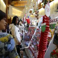 Yule pick one: People look at a Christmas card display at a Tokyo shopping mall Thursday. | BLOOMBERG