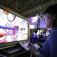 Wii'd out: An attendee plays a video game on a Nintendo Co. Wii U game console during the 2013 Tokyo Game Show at Chiba's Makuhari Messe convention center on Sept. 20. | BLOOMBERG