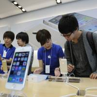 All-in-one: Staff explain the iPhone to customers at an Apple Inc. outlet in Tokyo. | BLOOMBERG