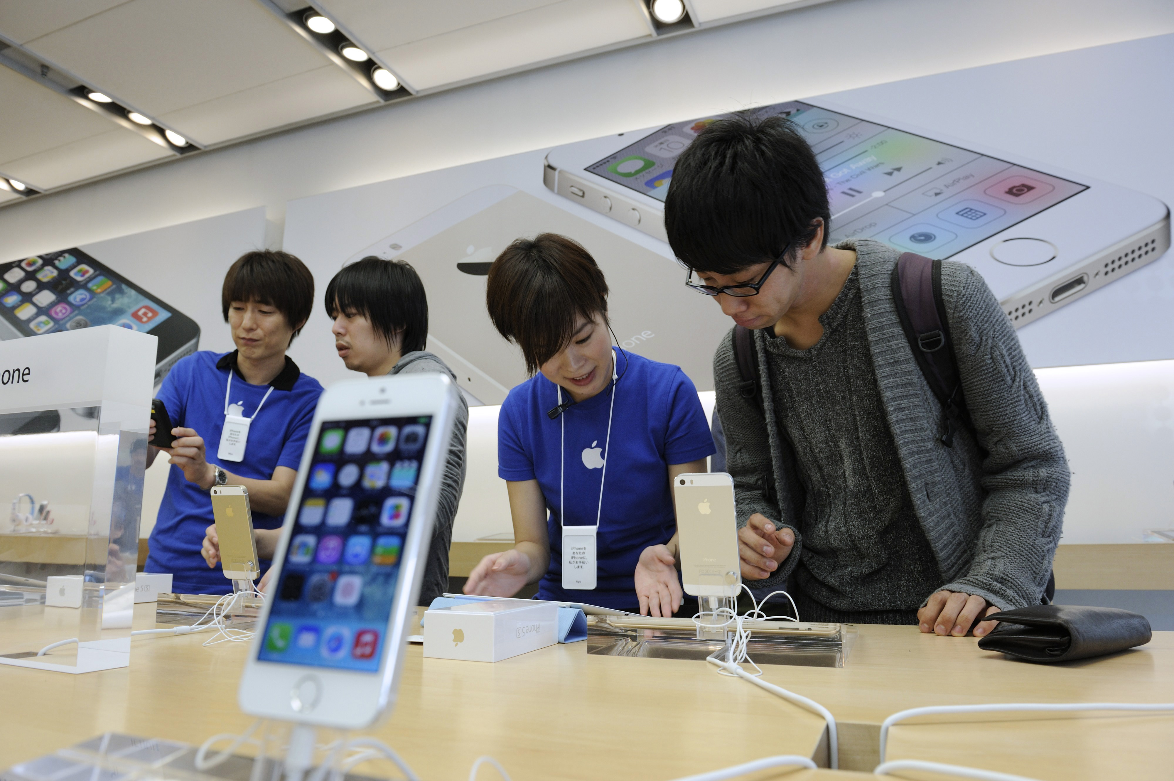 All-in-one: Staff explain the iPhone to customers at an Apple Inc. outlet in Tokyo.   BLOOMBERG