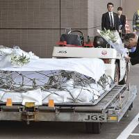 Unprecedented: JGC Corp. President Koichi Kawana (right) prepares to lay flowers on the coffin of a company official killed during January's Algerian hostage crisis. | KYODO