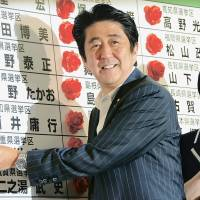 Smell of success: Prime Minister Shinzo Abe places rosettes next to the names of Liberal Democratic Party candidates who won seats in the July 21 Upper House election.   SATOKO KAWASAKI