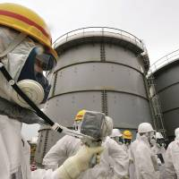 Hot water: A Tokyo Electric Power Co. employee measures radiation levels as journalists stand in front of storage tanks holding radioactive water at the Fukushima No. 1 plant on Nov. 7.   POOL