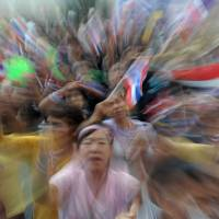 Vocal opposition: Thai anti-government protesters wave national flags as they rally at Government Complex in Bangkok on Sunday. The leader of mass opposition protests that have shaken the Thai capital called for a last-ditch effort to topple the government, vowing to surrender to the authorities if the action fails. | AFP-JIJI