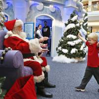 John Doris, 4, stretches out his arms to hug Santa Claus at the Ice Palace inside Cherry Creek Mall in Denver on Friday.   AP