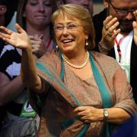 Back in: Presidential candidate Michelle Bachelet waves during a victory rally in Santiago on Sunday.   AP