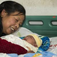 Drug scare: A woman cares for her grandson, who was recovering from a severe adverse reaction to a hepatitis B vaccination, in a hospital in Changde, southern China's Hunan province, on Dec. 12. Chinese health authorities have sent experts to investigate a drugmaker over safety concerns after several babies died shortly after receiving hepatitis B vaccines. | AP