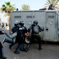 Riot act: Egyptian police detain a protester as they disperse a demonstration in Alexandria, Egypt, on Monday. Black clad riot police fired tear and chased dozens of rights activists and protesters who held a demonstration in the Mediterranean city demanding abolishing a new law that extensively restricted the right to hold a protest, imposing fines and jail terms on violators.   AP