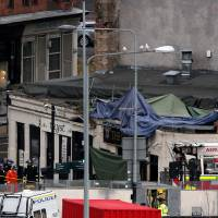 Emergency crews: Police officers and Scottish Fire and Rescue Services personnel work Saturday after a helicopter crashed onto the roof of The Clutha Bar in Glasgow the night before. | AP