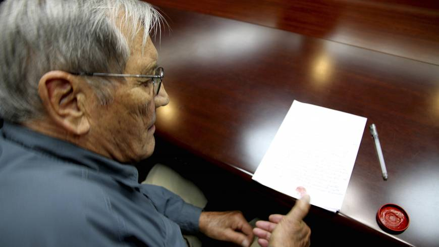 War of words: U.S. citizen Merrill Newman, 85, applies his thumb print to a document that North Korean authorities say was an apology Newman wrote and read in North Korea on Nov. 9. | AP