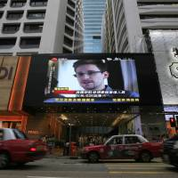 Larger than life: A huge television screen shows a news report on Edward Snowden, the former U.S. National Security Agency contractor who leaked top-secret documents about sweeping U.S. surveillance programs, outside a shopping mall in Hong Kong in June. | AP