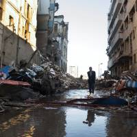 'Innocent blood': An Egyptian passes through the scene of a powerful explosion believed to be caused by a car bomb at a police headquarters building, that killed at least a dozen people, wounded more than 100, and left scores buried under the rubble, in the Nile Delta city of Mansoura on Tuesday. | AP
