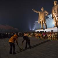 Sprucing up: As North Koreans arrive to pay their respects, women clean around the base of statues of late leaders Kim Il Sung (left) and Kim Jong Il in Pyongyang on Monday, the eve of the second anniversary of the death of Kim Jong Il. | AP