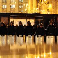 Reflecting anger: Ukrainian riot policemen stand guard in Kiev's Independence Square on Tuesday. Clashes. Police clashed with protesters and tore down their tents in the main square of the Ukrainian capital early Wednesday, in an escalation of a weeks-long standoff. | AFP-JIJI