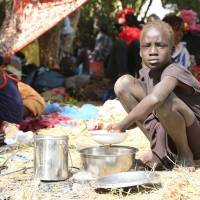 Young country: A girl prepares a lunch inside a United Nations compound on the outskirts of Juba on Tuesday following recent clashes by rival factions in the South Sudan capital. | AFP-JIJI