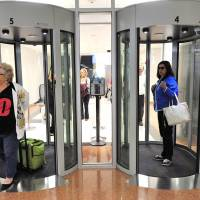 Traveling light: Passengers walk through security portals at the New Jersey's Atlantic City International Airport in November 2012. The Transportation Security Administration says that passengers left behind a record $531,395.22 in loose change at security checkpoints in 2012. | AP