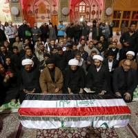 Fallen idols: Mourners pray over the coffin of an Iraqi Shiite fighter during his funeral in the Shiite holy city of Najaf, Iraq, on Nov. 29. A leading Shiite Muslim cleric widely followed by Iraqi militants has issued the first public religious edict permitting Shiites to fight in Syria's civil war alongside President Bashar Assad's forces.   AP