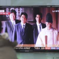 Prime time: People watch a TV news program Thursday on Prime Minister Shinzo Abe's visit to Yasukuni Shrine in Tokyo at a railway station in Seoul. | AP