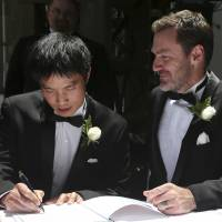 Newly wed: Ivan Hinton (right) watches as his partner, Chris Teoh, signs a wedding register after taking their vows in a ceremony at Old Parliament House in Canberra on Saturday. Dozens of gay and lesbian couples from all around Australia are taking advantage of a new law in the Australia Capital Territory that allows same-sex marriages. But the unions may be short-lived if the High Court on Thursday finds in favor of a challenge to overrule the law. | AP