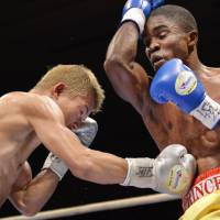 In control: Tomoki Kameda lands a punch to Namibian challenger Immanuel Naidjala's ribs during Tuesday's WBO bantamweight title fight in Osaka. Kameda retained his title by unanimous decision. | KYODO